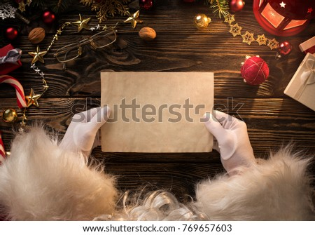 Close up of Santa Claus hands holding, reading blank letter with copy space #769657603