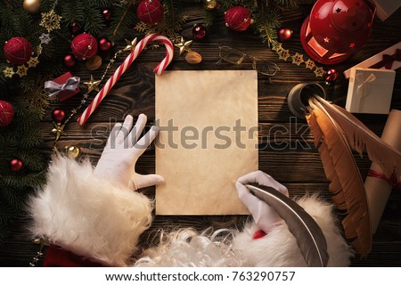 Close up of Santa Claus hands writing letter on Worden desk with copy space #763290757