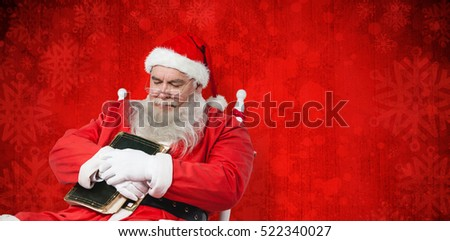 Close-up of Santa Claus holding bible while sleeping on chair against red paint splatter background #522340027