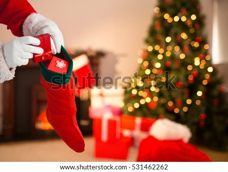 Close-up of Santa Claus putting gift boxes in Christmas stocking #531462262