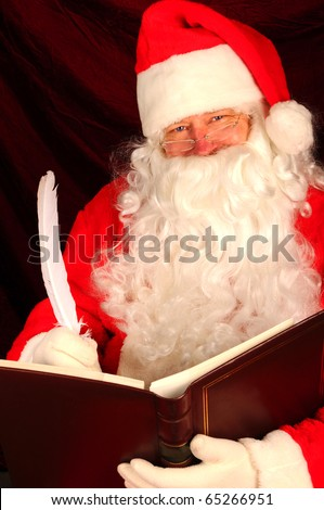 Close up of Santa Claus writing with a quill pen in a large leather bound book. Vertical format