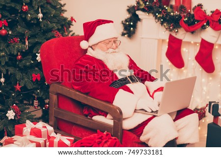 Close up of santa, study list of children's wishes and gifts on device, ready to make dreams come true, bring happiness to kids. Holly jolly x mas, noel coming #749733181