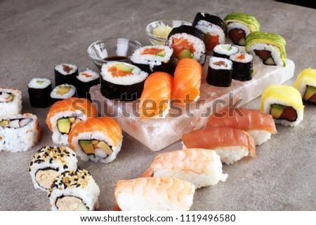 close up of sashimi sushi set with chopsticks and soy - sushi roll with salmon and sushi roll with smoked eel, selective focus.