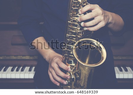 close up of saxophone Player hands  playing alto sax musical instrument over piano  background  ,  closeup with copy space, vintage tone,  can be used for music background