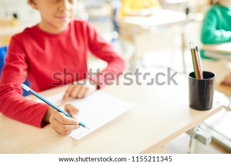 Close-up of schoolboy holding pencil and writing in paper while taking test at class