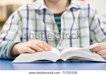 Close Up Of Schoolboy Studying Textbook In Classroom