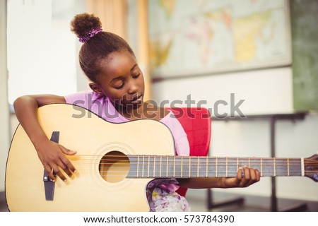 Close up of schoolgirl playing guitar in classroom at school