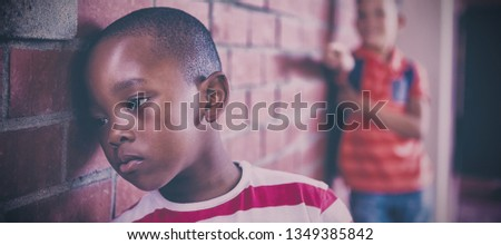 Close-up of schoolkid bullying a sad boy in corridor at school