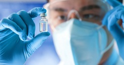 close up of scientist microbiologist or medical worker look to newest vaccine in the laboratory