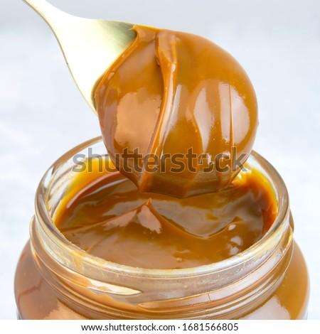 Close-up of scoop and jar full of dulce de leche or dulce de leche Foto stock ©