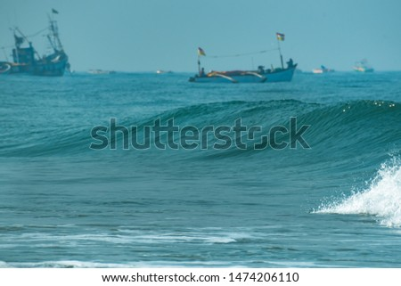 Close up of sea waves with defocused fishing boats in the background. Morning outdoor picture of ocean high tide waters in summer, tropical beach vacation destination. Colva, Goa, India
