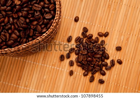 Close up of seeds in front of a basket full of coffee seeds