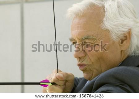 Close up of senior businessman using bow and arrow