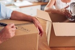 Close Up Of Senior Couple Downsizing In Retirement Boxes Ready For Move Into New Home
