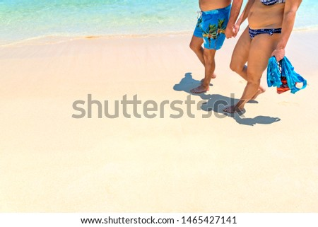 Close up of senior couple in swim suit walking on golden sand beach in summer season. Happy romantic Caucasian man and woman hand in hand enjoy vacation. Travel vacation retirement lifestyle concept. #1465427141