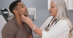 Close up of senior female doctor examining male patients neck