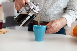 Close up of senior man pouring hot coffee from french press in kitchen during breakfast. Elderly person in the morning enjoying fresh brown cafe espresso cup caffeine from vintage mug, filter relax