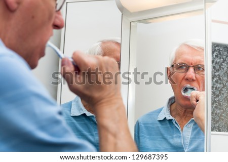 Close up of senior man reflected in mirror brushing his teeth.