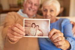 Close up of senior's hands holding up an old photograph of themselves, when they were young while sitting on their vintage living room couch at home