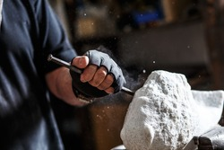 Close up of senior sculptor hands working on his marble sculpture in his workshop with hammer and chisel.