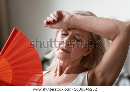Close up of senior woman feel unwell suffer from hot weather heatstroke have no air conditioner at home, elderly unhealthy female pensioner struggle with heat use hand fan or waver cooling down