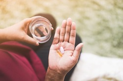 Close Up Of Senior woman holding Calcium supplement tablet pills and Omega 3 oil with glass of water.Nutritional Supplements.Sport,Diet Concept.Capsules Vitamin And Dietary Supplements.