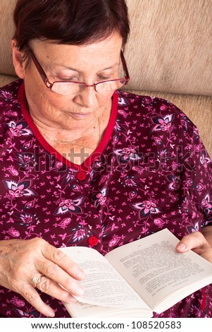 Close up of senior woman sitting on sofa and reading book.