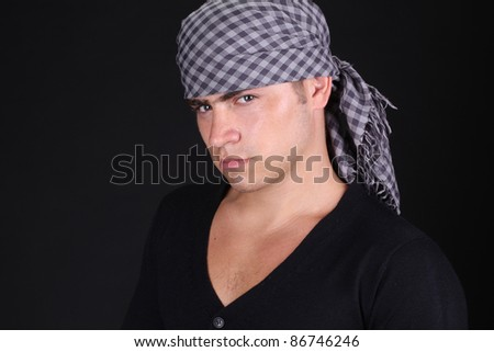 Close up of serious looking man with headscarf over dark background