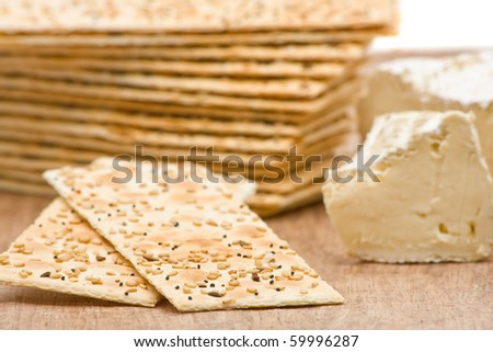 Close up of sesame crackers with cream cheese on wooden background