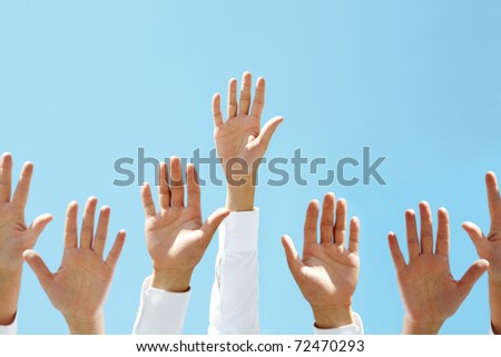 Close-up of several human hands raised against clear blue sky