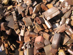 Close-up of several old and worn padlocks in the fountain of the padlocks of the city of Montevideo. Tradition of locking locks metal padlocks to seal the love of couples, illuminated by the sun.