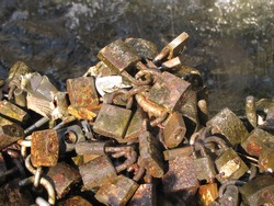Close-up of several old and worn padlocks with water background of the a fountain of the city of Montevideo. Tradition of locking locks metal padlocks to seal the love of couples, by the sun light.