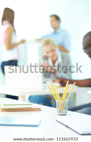 Close-up of several pencils in plastic glass on background of group of students working
