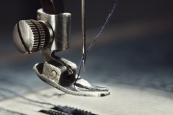 Close up of sewing machine needle with thread. Working part of antique sewing machine.