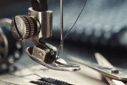 Close up of sewing needle. Tailoring scissors on working part of antique sewing machine.