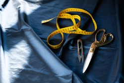 Close-up of sewing supplies. Scissors, wire cutters, an orange measuring tape lie on a fabric table