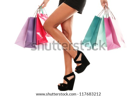 Close up of sexy woman legs in shoes and shopping bags isolated on a white