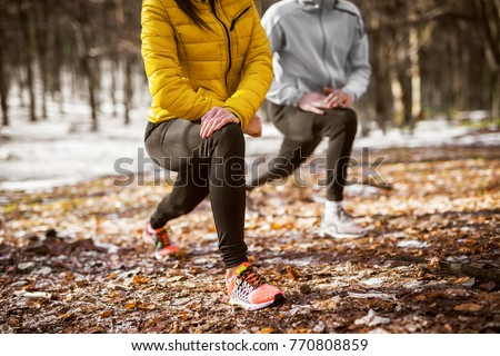 Close up of shape fitness girl in sportswear doing leg stretching with her personal trainer in the forest in the sunny winter morning.