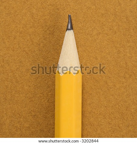 Close up of sharp pencil tip on tan background.