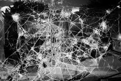 Close up of shattered glass. Broken screen defocused. Shattering window glass pieces. Car windshiled broken texture. Soft focus.