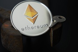 Close up of sheeny Ethereum coin and metal key on rusty vintage nippers. Cryptocurrency key code, secure Ethereum wallets concept. Black background selective focus with copy space