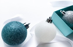 Close-up of shiny Christmas balls blue turquoise, white and silver color with ribbon and blue gift box on a white background. The concept of Christmas and holiday eve. Copy space