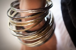 Close-up of shiny golden-silver colored bracelets bangles around a woman's wrist hand