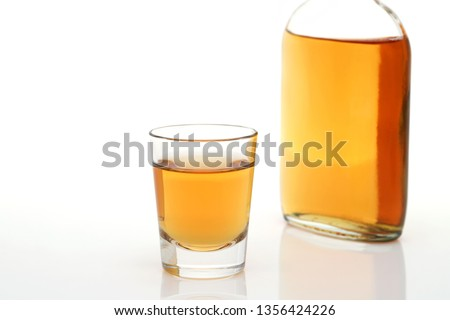 close up of shot glass and pocket bottle of whiskey on white background #1356424226
