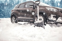 close up of shovel near car. auto blurred on background. transportation, winter, vehicle stuck in the snow. concept.