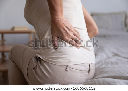 Close up of sick unwell old woman sit on bed touch lower back suffer from backache, unhealthy elderly female massage spine struggle with arthritis, have pinched stiff nerve, senior healthcare concept