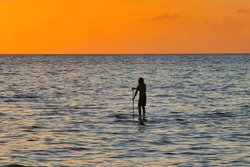 Close-up of silhouetted young surfer girl on a stand up paddleboard on Maui.