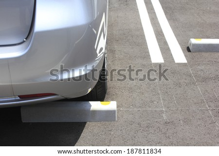 close up of silver car parked in parking spot