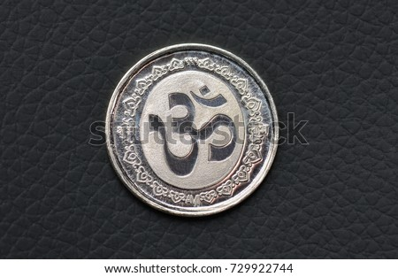 Close up of silver coin etched with Hindu religious symbol Om. #729922744
