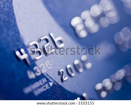 Close-up of silver digits on a credit card.  Very shallow depth of field, focus on number 2.  You can see the texture of the card in the in-focus areas.